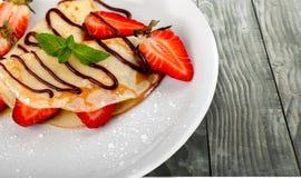 Heerlijke pannekoeken met chocolade op witte plaat Stock Fotografie
