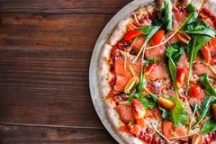 Heerlijke pizza op hoogste mening Yummy pizza met tomaten, groenten, kaas en rookzalm op houten lijst bij pizzeria It'€™ royalty-vrije stock afbeeldingen