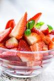 Heerlijke plakken van organische aardbeien in een kop stock foto's
