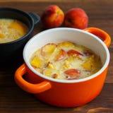 Heerlijke pudding met perzik in braadpan, close-up stock afbeeldingen