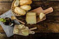Heerlijke rijpe kaas met knapperige baguette en wijn Royalty-vrije Stock Foto's