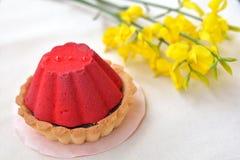 Heerlijke, rode cake met chocolade het vullen dichtbij gele bloemen Stock Afbeeldingen