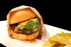 Heerlijke rundvleeshamburger op zwarte achtergrond Royalty-vrije Stock Fotografie
