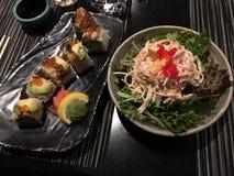 Heerlijke sushi met zeevruchtensalade stock afbeeldingen