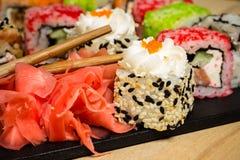 Heerlijke sushibroodjes die op zwarte raad met eetstokjes worden gediend royalty-vrije stock foto