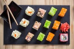 Heerlijke sushibroodjes die op zwarte raad met eetstokjes worden gediend stock foto