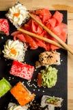 Heerlijke sushibroodjes die op zwarte raad met eetstokjes worden gediend royalty-vrije stock afbeelding