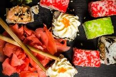 Heerlijke sushibroodjes die op zwarte raad met eetstokjes worden gediend royalty-vrije stock fotografie