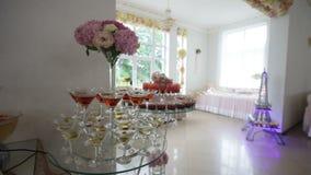 Heerlijke verfraaide snoepjes en vruchten op lijsten voor huwelijksontvangst, de catering van de cocktailspartij in restaurant stock videobeelden