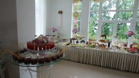 Heerlijke verfraaide snoepjes en vruchten op lijsten voor huwelijksontvangst, de catering van de cocktailspartij in restaurant stock video