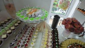 Heerlijke verfraaide snoepjes op buffetlijst, de catering van de cocktailspartij stock footage