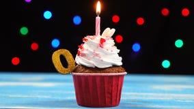 Heerlijke verjaardag cupcake met het branden van kaars en nummer 0 op multicolored vage lichtenachtergrond stock videobeelden