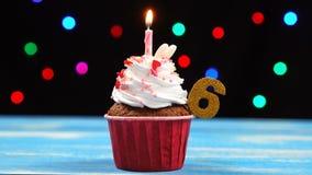 Heerlijke verjaardag cupcake met het branden van kaars en nummer 6 op multicolored vage lichtenachtergrond stock videobeelden
