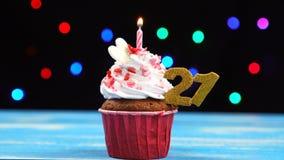 Heerlijke verjaardag cupcake met het branden van kaars en nummer 21 op multicolored vage lichtenachtergrond stock video