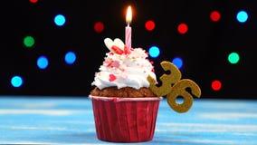 Heerlijke verjaardag cupcake met het branden van kaars en nummer 36 op multicolored vage lichtenachtergrond stock videobeelden