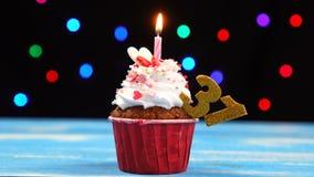 Heerlijke verjaardag cupcake met het branden van kaars en nummer 31 op multicolored vage lichtenachtergrond stock videobeelden
