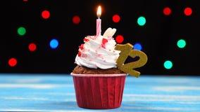 Heerlijke verjaardag cupcake met het branden van kaars en nummer 12 op multicolored vage lichtenachtergrond stock footage