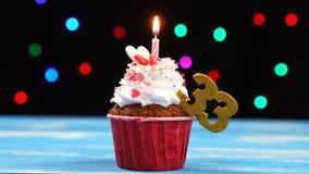 Heerlijke verjaardag cupcake met het branden van kaars en nummer 33 op multicolored vage lichtenachtergrond stock footage