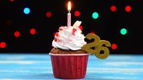 Heerlijke verjaardag cupcake met het branden van kaars en nummer 26 op multicolored vage lichtenachtergrond stock videobeelden