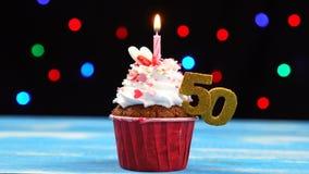 Heerlijke verjaardag cupcake met het branden van kaars en nummer 50 op multicolored vage lichtenachtergrond stock footage