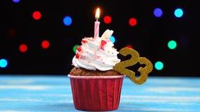 Heerlijke verjaardag cupcake met het branden van kaars en nummer 23 op multicolored vage lichtenachtergrond stock video