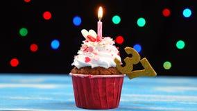 Heerlijke verjaardag cupcake met het branden van kaars en nummer 37 op multicolored vage lichtenachtergrond stock videobeelden
