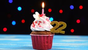 Heerlijke verjaardag cupcake met het branden van kaars en nummer 22 op multicolored vage lichtenachtergrond stock video