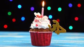 Heerlijke verjaardag cupcake met het branden van kaars en nummer 34 op multicolored vage lichtenachtergrond stock videobeelden