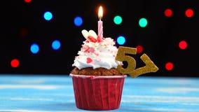 Heerlijke verjaardag cupcake met het branden van kaars en nummer 57 op multicolored vage lichtenachtergrond stock videobeelden