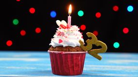 Heerlijke verjaardag cupcake met het branden van kaars en nummer 32 op multicolored vage lichtenachtergrond stock footage