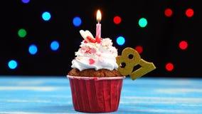 Heerlijke verjaardag cupcake met het branden van kaars en nummer 81 op multicolored vage lichtenachtergrond stock videobeelden