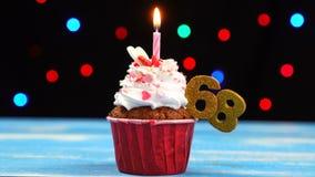 Heerlijke verjaardag cupcake met het branden van kaars en nummer 68 op multicolored vage lichtenachtergrond stock videobeelden