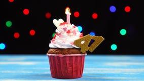 Heerlijke verjaardag cupcake met het branden van kaars en nummer 41 op multicolored vage lichtenachtergrond stock videobeelden