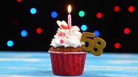 Heerlijke verjaardag cupcake met het branden van kaars en nummer 58 op multicolored vage lichtenachtergrond stock videobeelden