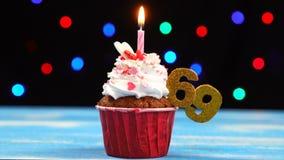 Heerlijke verjaardag cupcake met het branden van kaars en nummer 69 op multicolored vage lichtenachtergrond stock video