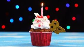 Heerlijke verjaardag cupcake met het branden van kaars en nummer 84 op multicolored vage lichtenachtergrond stock footage