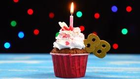 Heerlijke verjaardag cupcake met het branden van kaars en nummer 88 op multicolored vage lichtenachtergrond stock video