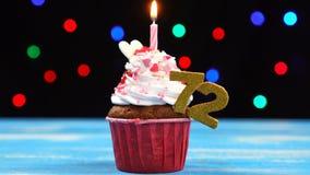 Heerlijke verjaardag cupcake met het branden van kaars en nummer 72 op multicolored vage lichtenachtergrond stock footage