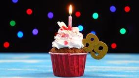 Heerlijke verjaardag cupcake met het branden van kaars en nummer 89 op multicolored vage lichtenachtergrond stock videobeelden