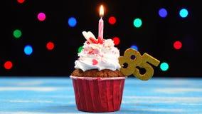 Heerlijke verjaardag cupcake met het branden van kaars en nummer 85 op multicolored vage lichtenachtergrond stock video