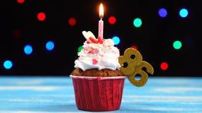 Heerlijke verjaardag cupcake met het branden van kaars en nummer 86 op multicolored vage lichtenachtergrond stock videobeelden