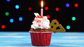Heerlijke verjaardag cupcake met het branden van kaars en nummer 87 op multicolored vage lichtenachtergrond stock videobeelden