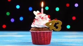 Heerlijke verjaardag cupcake met het branden van kaars en nummer 43 op multicolored vage lichtenachtergrond stock video