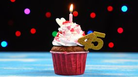 Heerlijke verjaardag cupcake met het branden van kaars en nummer 45 op multicolored vage lichtenachtergrond stock footage