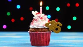 Heerlijke verjaardag cupcake met het branden van kaars en nummer 46 op multicolored vage lichtenachtergrond stock video