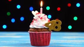 Heerlijke verjaardag cupcake met het branden van kaars en nummer 48 op multicolored vage lichtenachtergrond stock videobeelden