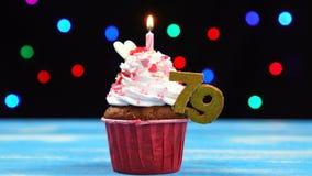 Heerlijke verjaardag cupcake met het branden van kaars en nummer 79 op multicolored vage lichtenachtergrond stock footage