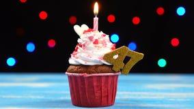 Heerlijke verjaardag cupcake met het branden van kaars en nummer 47 op multicolored vage lichtenachtergrond stock video