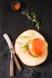 Heerlijke verse eigengemaakte hamburger op donkere dienende raad met kruidig Stock Fotografie