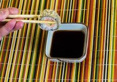 Heerlijke verse sushi in het paneren over een kom met sojasaus op een bamboedoek stock fotografie